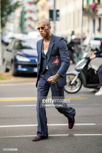Guest wears black sunglasses, a silver piercing, a gold chain necklace with cross pendant, a white ribbed V-neck tank-top, a navy blue buttoned...