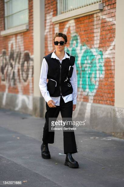 Guest wears black sunglasses, a white shirt, a black cargo sleeveless zipper jacket, black flared pants, black shiny leather ankle boots, a gold...