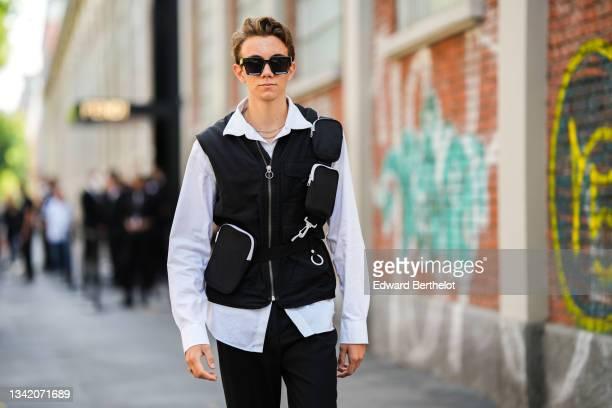 Guest wears black sunglasses, a white shirt, a black cargo sleeveless zipper jacket, black flared pants, a gold Chanel ring, outside the Fendi...