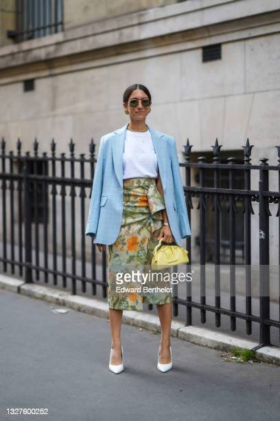 Guest wears black sunglasses, a white t-shirt, a pale blue checkered pattern long blazer jacket, gold necklaces, gold earrings, a silver bracelet, a...