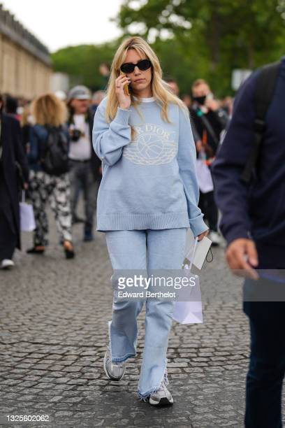 Guest wears black sunglasses, a white t-shirt, a pale blue with a white Dior logo sweater, blue faded ripped split denim jeans pants, gray and white...