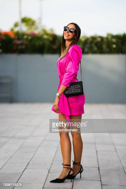 Guest wears black sunglasses, diamond earrings, a gold chain necklace, a pink fuchsia V-neck / puffy shoulders / long sleeves / knotted / ruffled...