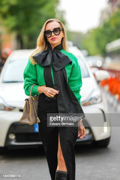 Guest wears black sunglasses from Prada, a black large knotted scarf as a necklace, a green ribbed wool cropped pullover, a gold watch, a large gold...