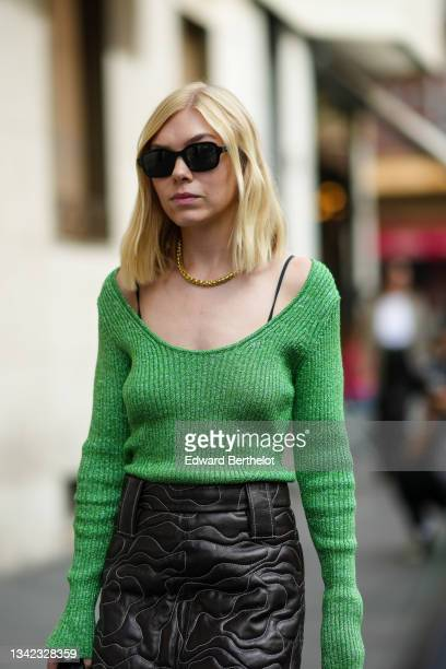 Guest wears black sunglasses, gold earrings, a gold chain necklace, a green ribbed wool long sleeves pullover, a black shiny leather embroidered...