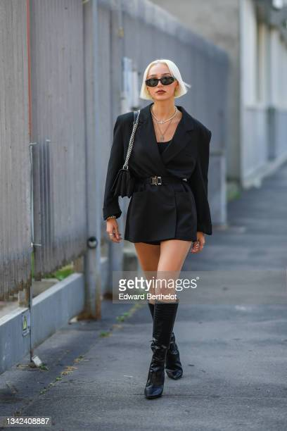 Guest wears black sunglasses, gold earrings, silver and pearls necklaces, a black blazer jacket with epaulets, a black shiny leather belt, a black...