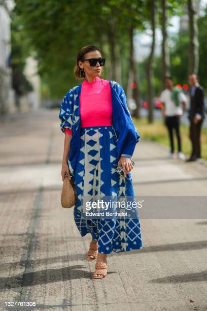 Guest wears black sunglasses, gold pendant earrings, a fuchsia pink ribbed turtleneck long sleeves t-shirt, a blue with white print pattern oversized...