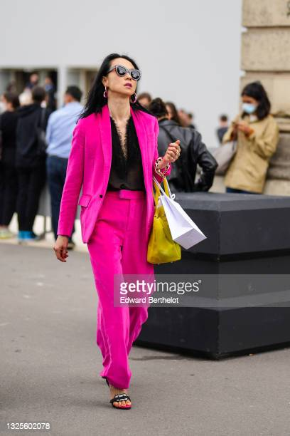 Guest wears black sunglasses, pink and silver earrings, a black V-neck t-shirt with feathers on the collar, a pink fuchsia blazer jacket, matching...