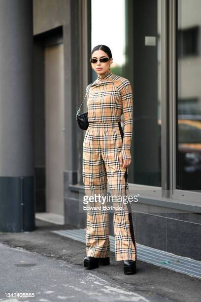 Guest wears black sunglasses, silver earrings, a beige with red / white / black checkered print pattern high zipper neck long sleeves pullover from...