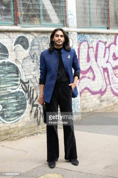 A guest wears black velvet trousers black T shirt and boots with a blue jacket during London Fashion Week Men's June 2019 on June 09 2019 in London...