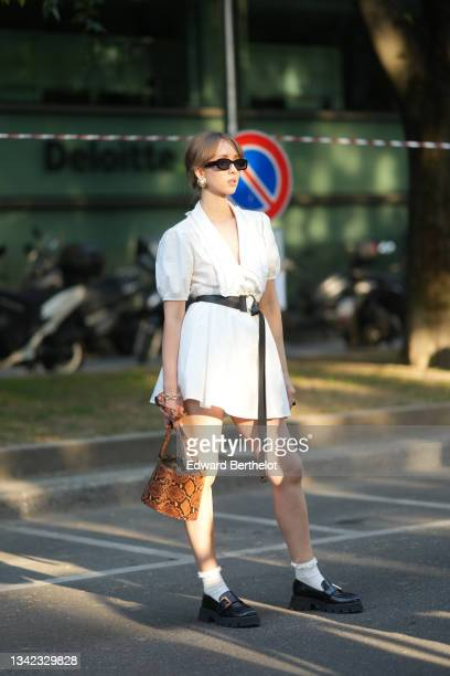 Guest wears black vintage sunglasses, gold large and large pearl earring, a white V-neck / puffy sleeves / short dress, a black shiny leather belt, a...
