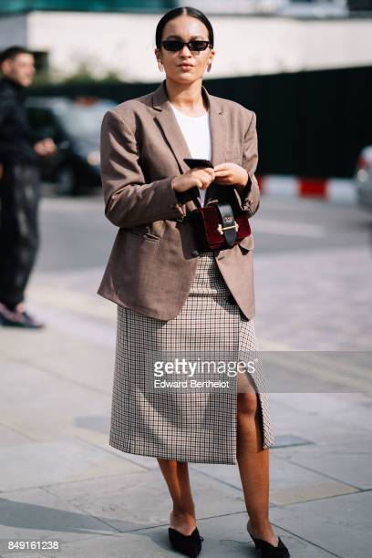 A guest wears blazer jacket a gingham skirt a Prada bag outside Versus during London Fashion Week September 2017 on September 17 2017 in London...
