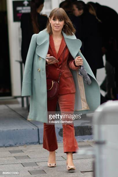 A guest wears blue coat a red suit and attends Le Defile L'Oreal Paris as part of Paris Fashion Week Womenswear Spring/Summer 2018 at Avenue Des...