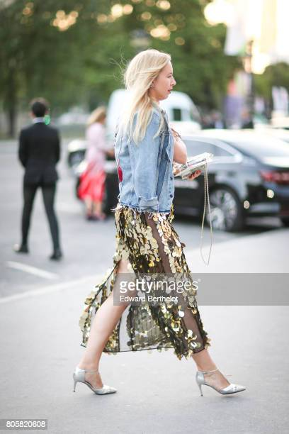 A guest wears blue denim jacket and a lace dress and heels outside the amfAR dinner at Petit Palais during Paris Fashion Week Haute Couture...