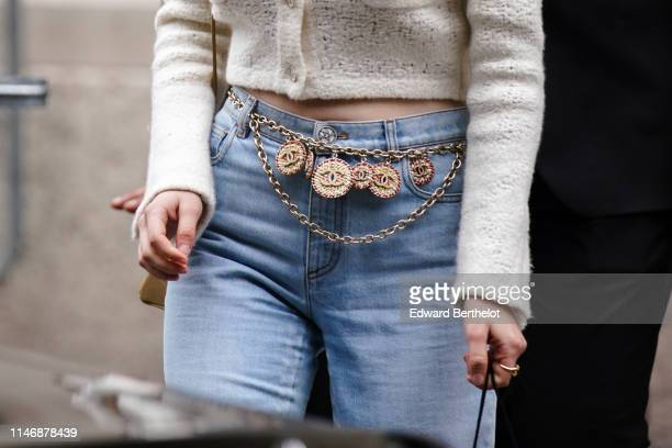 A guest wears blue denim jeans a Chanel metallic chain belt with logos outside the Chanel Cruise Collection 2020 At Grand Palais on May 03 2019 in...