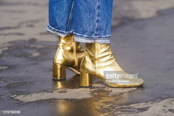Guest wears blue denim jeans and golden shiny boots, outside Chanel, during Paris Fashion Week - Womenswear Fall/Winter 2020/2021 on March 03, 2020...