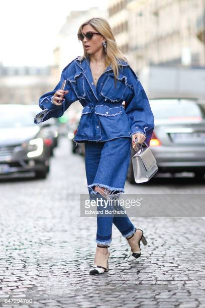A guest wears blue denim ripped jeans pants and a blue denim jacket outside the Alexis Mabille show during Paris Fashion Week Womenswear Fall/Winter...