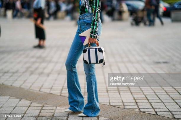 Guest wears blue flare denim pants, a black and white bag, outside Louis Vuitton, during Paris Fashion Week - Womenswear Spring Summer 2020, on...