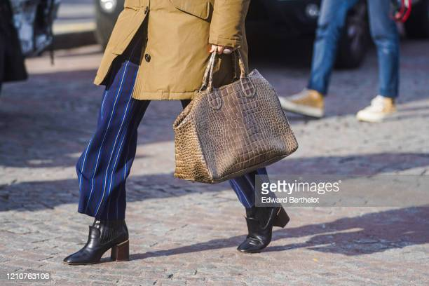 A guest wears blue flowing striped pants black leather pointy shoes a brown leather crocodile leather bag outside Chanel during Paris Fashion Week...