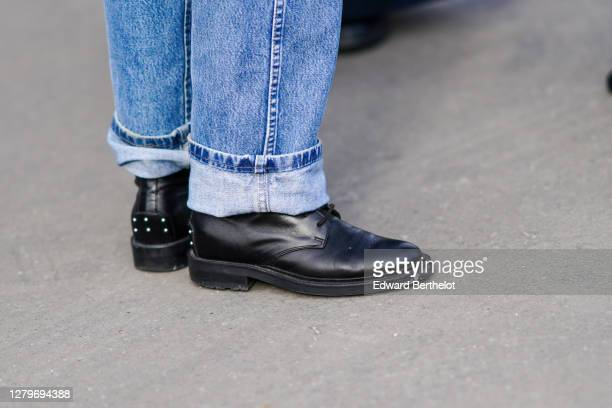 Guest wears blue jeans with hems, black leather shoes, outside Chanel, during Paris Fashion Week - Womenswear Spring Summer 2021, on October 06, 2020...