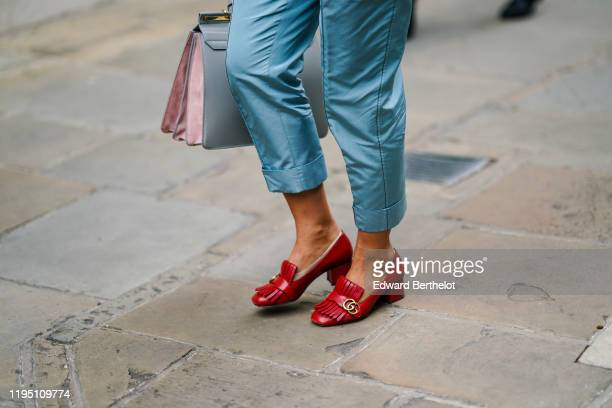 Guest wears blue lustrous cropped pants and red Gucci shoes, during London Fashion Week September 2019 on September 16, 2019 in London, England.