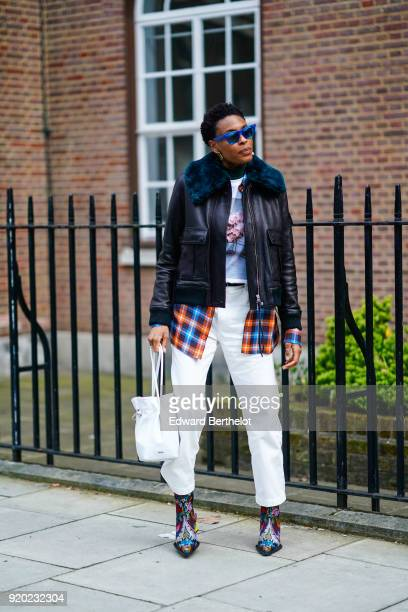 A guest wears blue sunglasses a black leather jacket with blue fur white pants a white bag a checked shirt flower print shoes during London Fashion...