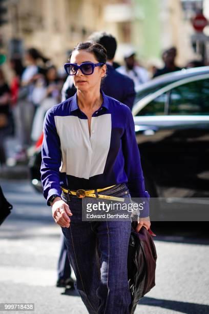 A guest wears blue sunglasses a blue and white shirt a golden belt outside Dior during Paris Fashion Week Menswear SpringSummer 2019 on June 23 2018...