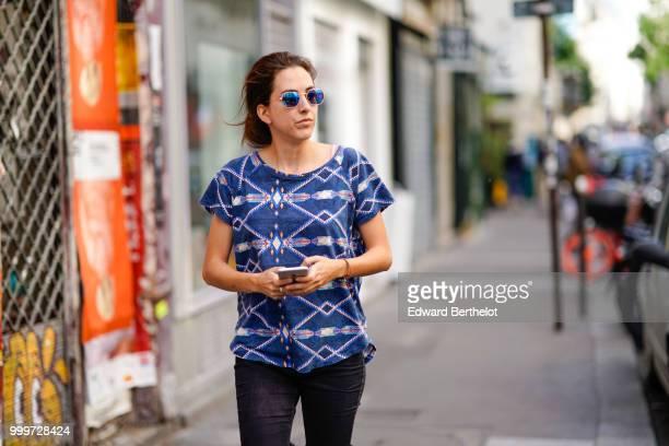 A guest wears blue sunglasses a blue tshirt with printed patterns outside Yohji Yamamoto during Paris Fashion Week Menswear SpringSummer 2019 on June...