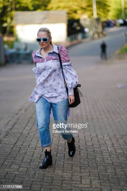 Guest wears blue sunglasses, a floral print shirt with an old pink ruffle, a black bag , washed-out blue denim cuffed pants, shiny black ankle-boots...
