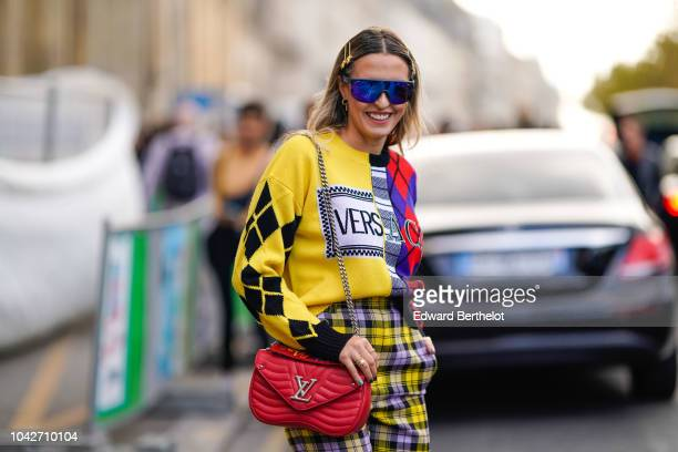 A guest wears blue sunglasses a yellow and red pullover a red Vuitton bag checked pants outside Andrew GN during Paris Fashion Week Womenswear...