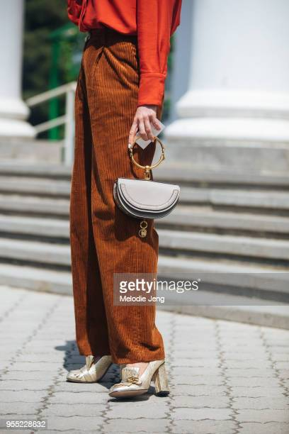 Guest wears brown corduroy pants, a salmon top, and Chloe bag on May 5, 2018 in Tbilisi, Georgia.