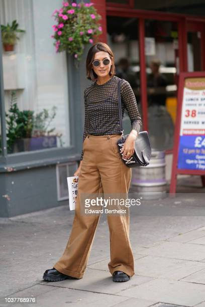 Guest wears brown flare pants, a black mesh top, during London Fashion Week September 2018 on September 15, 2018 in London, England.