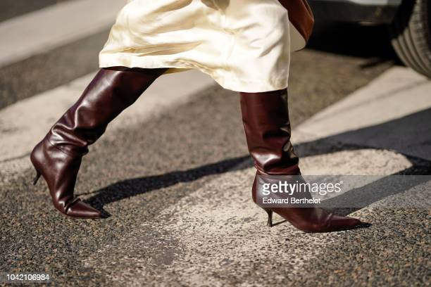 A guest wears brown leather boots outside Chloe during Paris Fashion Week Womenswear Spring/Summer 2019 on September 27 2018 in Paris France