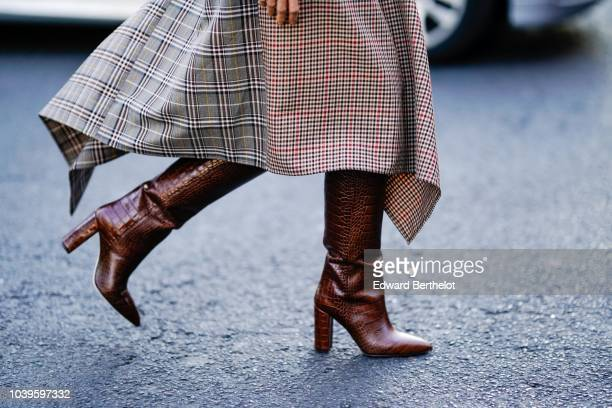 A guest wears brown leather boots outside Gucci during Paris Fashion Week Womenswear Spring/Summer 2019 on September 24 2018 in Paris France