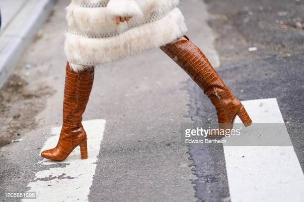 Guest wears brown leather crocodile pattern boots, outside Longchamp, during New York Fashion Week Fall-Winter 2020, on February 08, 2020 in New York...