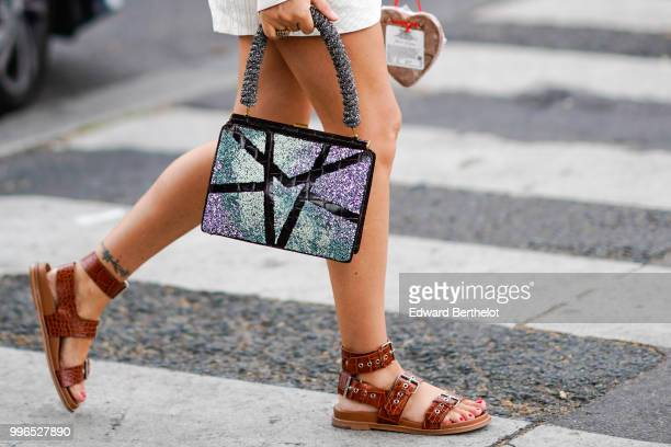 A guest wears brown leather sandals a silver glitter bag outside Vetements during Paris Fashion Week Haute Couture Fall Winter 2018/2019 on July 1...