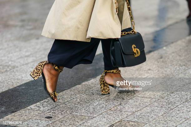 A guest wears brown leopard print shoes a black leather bag with golden metallic parts outside Miu Miu during Paris Fashion Week Womenswear Spring...
