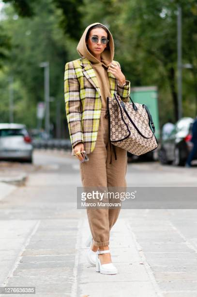 Guest wears brown pants and cape, a checkered jacket, a Gucci bag and high heels white shoes outside Sportmax's fashion show during the Milan Women's...