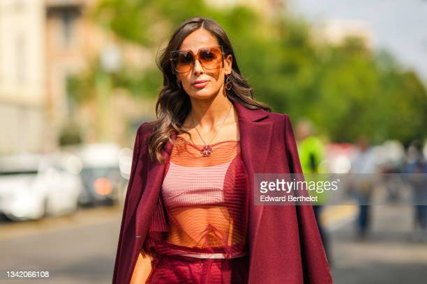 Guest wears brown sunglasses, gold and black pendants earrings, a matching gold chain with black pendant necklace, a white ribbed cropped top, a...