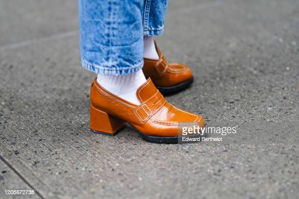Guest wears brown/orange leather shoes, white wool socks, during New York Fashion Week Fall Winter 2020, on February 11, 2020 in New York City.