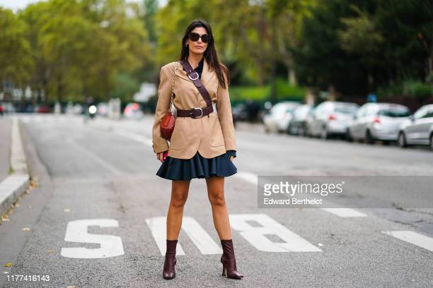 Guest wears Burberry sunglasses, earrings, a brown belt, a red bag, a camel jacket, a navy blue flowing mini circle dress, brown boots, outside Ann...