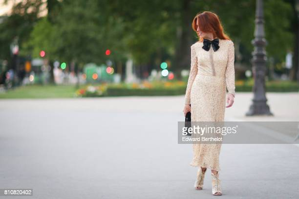 A guest wears camel dress with embroidery and a black bow tie outside the amfAR dinner at Petit Palais during Paris Fashion Week Haute Couture...