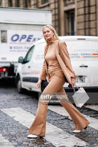 Guest wears camel turtleneck, jacket, flare pants, white shoes, outside Nobi Talai, during Paris Fashion Week Womenswear Fall/Winter 2019/2020, on...