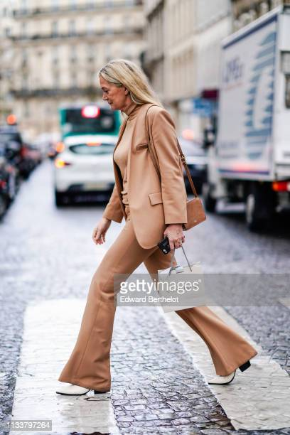 A guest wears camel turtleneck jacket flare pants white shoes outside Nobi Talai during Paris Fashion Week Womenswear Fall/Winter 2019/2020 on March...