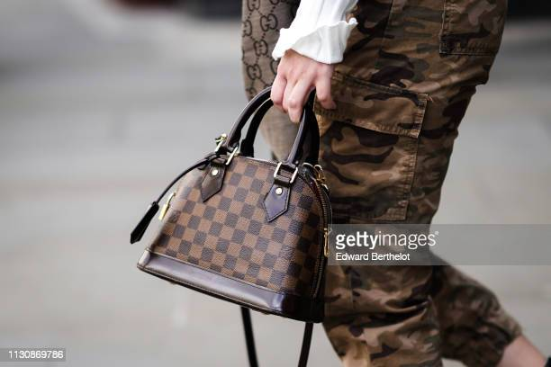 A guest wears camouflage print pants a Louis Vuitton bag during London Fashion Week February 2019 on February 19 2019 in London England
