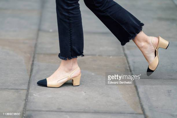 A guest wears Chanel beige and black slingback pumps black ripped hem pants during London Fashion Week February 2019 on February 16 2019 in London...