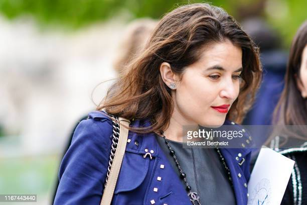 A guest wears Chanel earrings a Chanel necklace a black leather dress a blue trench coat with studded collar and lapels outside the Chanel Cruise...