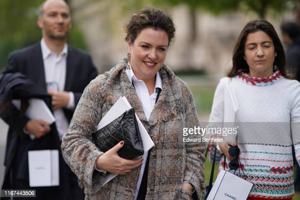 A guest wears Chanel earrings a white shirt a Chanel brown and grey fringed tweed coat a black Chanel clutch outside the Chanel Cruise Collection...