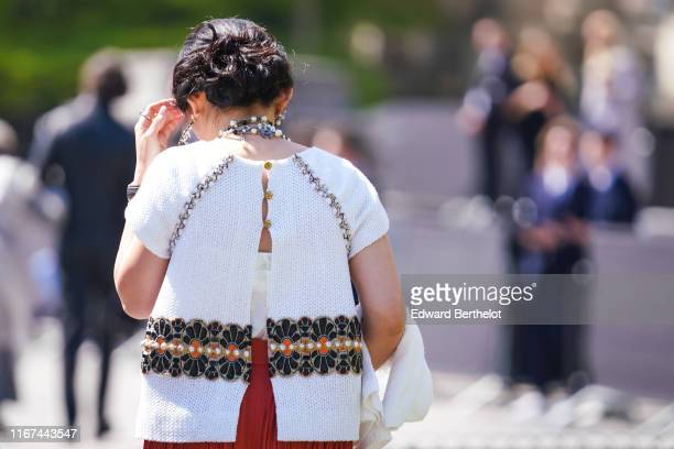A guest wears Chanel earrings Chanel necklaces a white Chanel top with embroideries at the waist and opened in the back outside the Chanel Cruise...