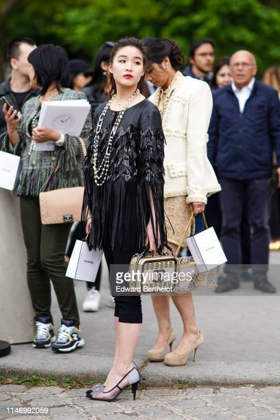 A guest wears Chanel necklaces a Chanel black leather fringed top black capris a Chanel vanity bag Chanel transparent heeled camellia pumps outside...