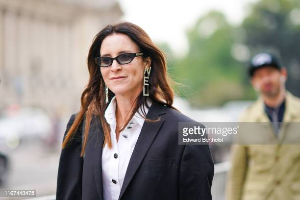A guest wears Chanel sunglasses Chanel rhinestone earrings a Chanel white shirt outside the Chanel Cruise Collection 2020 At Grand Palais on May 03...